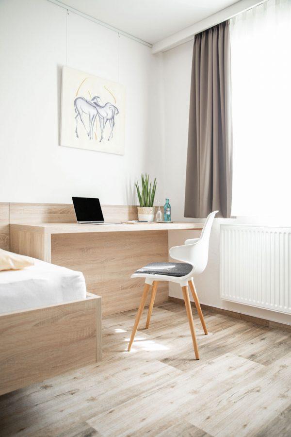 Blick ins Zimmer mit Stuhl vor Schreibtisch